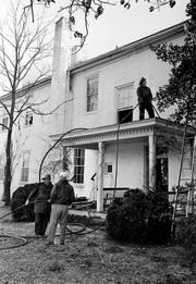Standing on the roof of a veranda at Travellers' Rest, a firefighter searches for ways to reach the fire blazing in the attic of the historic old mansion Jan. 4, 1969. Firefighter crews had the blaze under control in a matter of minutes.