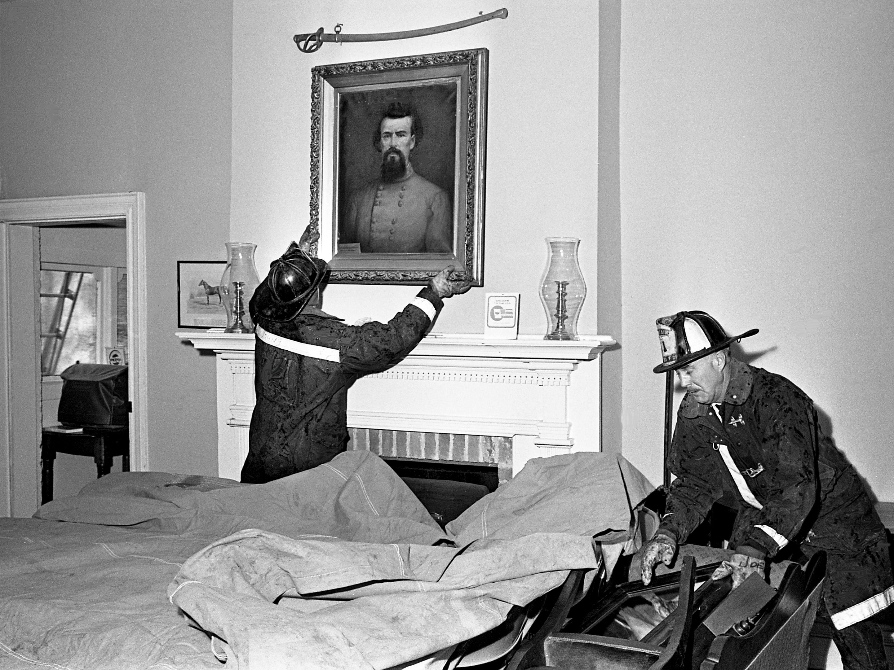 A firefighter removes a painting of Confederate Gen. Nathan Bedford Forrest from the wall to protect it from smoke and water damage as another starts cleanup operations after putting out an attic fire at the historic Travellers' Rest on Jan. 4, 1969.