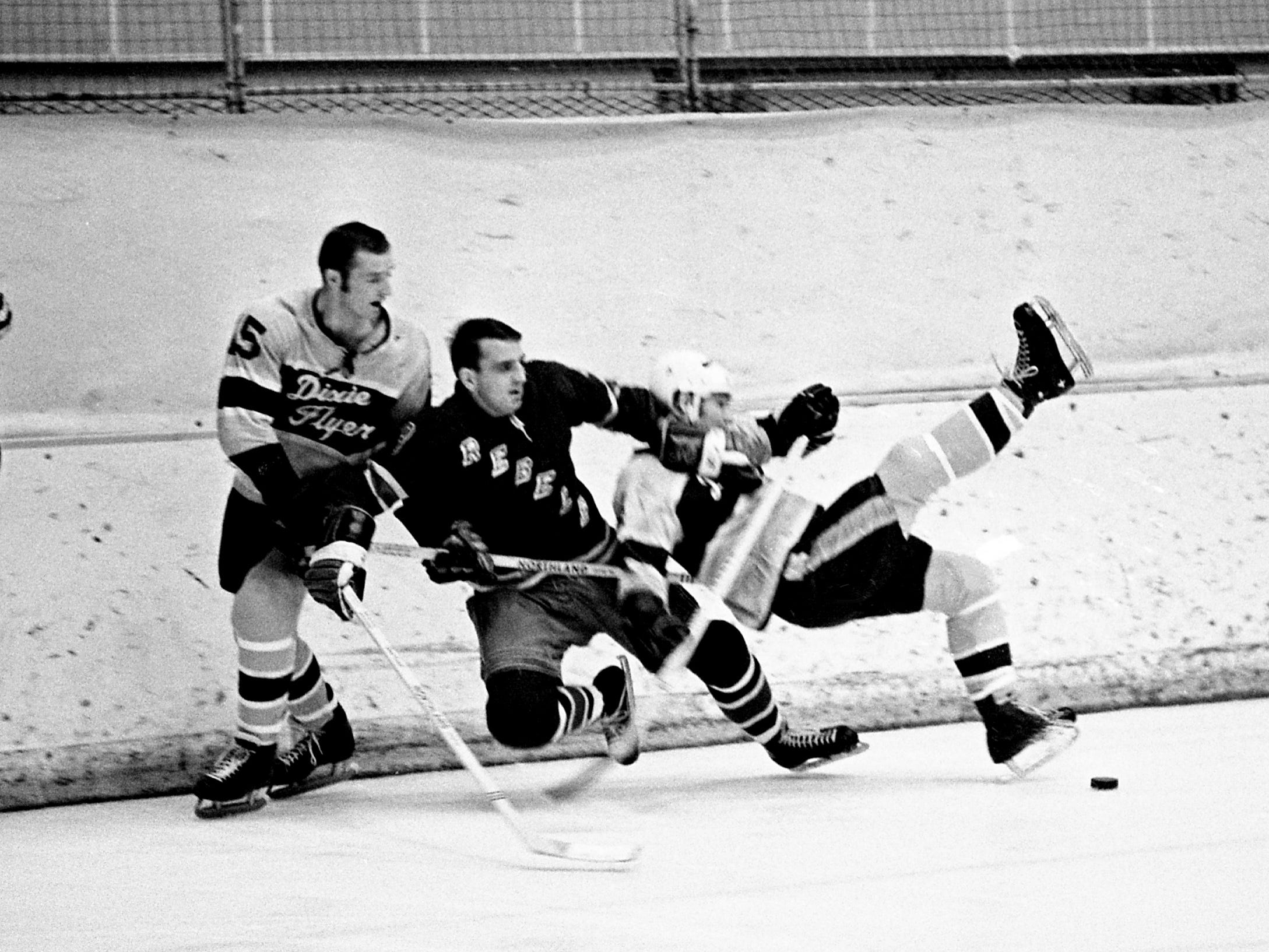 Salem Rebels' Don Rozich, center, pulls down Nashville Dixie Flyers defenseman Flo Pilote, right, while Pilote's teammate Don Borgeson (15) attempts to help out. The Flyers defeated Salem 4-2 before 2,847 fans at Municipal Auditorium on Jan. 11, 1969.
