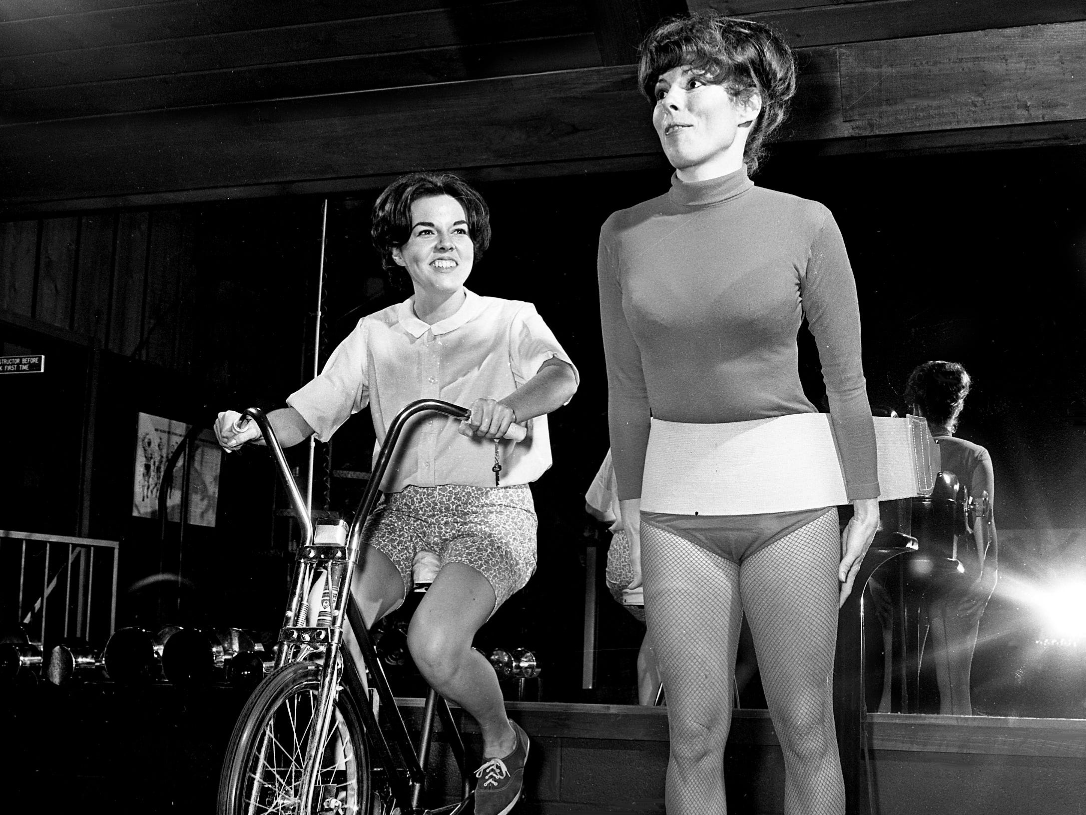 Tennessean reporter Candy McCampbell, left, works out during a visit to the Cosmopolitan Health Spa in Green Hills on Jan. 8, 1969, for a story on starting exercise for the new year. Spa member Mrs. Tom Coplin uses the vibrator belt for some spot reducing.