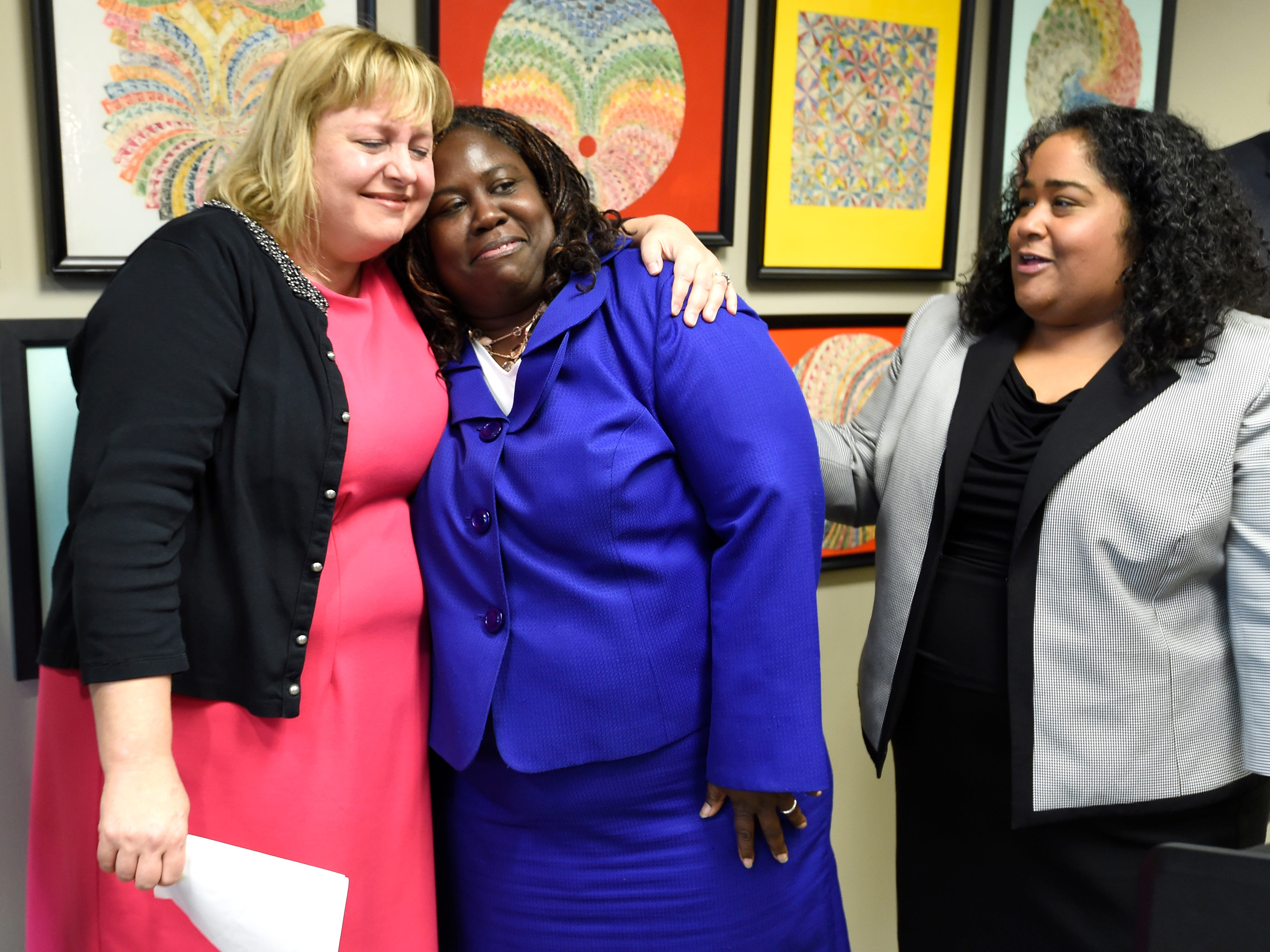 Juvenile Court Administrator Kathy Sinback hugs Judge Sheila Calloway with State Sen. Raumesh Akbari , D-Memphis, at a press conference Monday, Jan. 7, 2019, in Nashville, Tenn., after Gov. Bill Haslam granted full clemency to Cyntoia Brown, and set an Aug. 7 release date for her from prison.