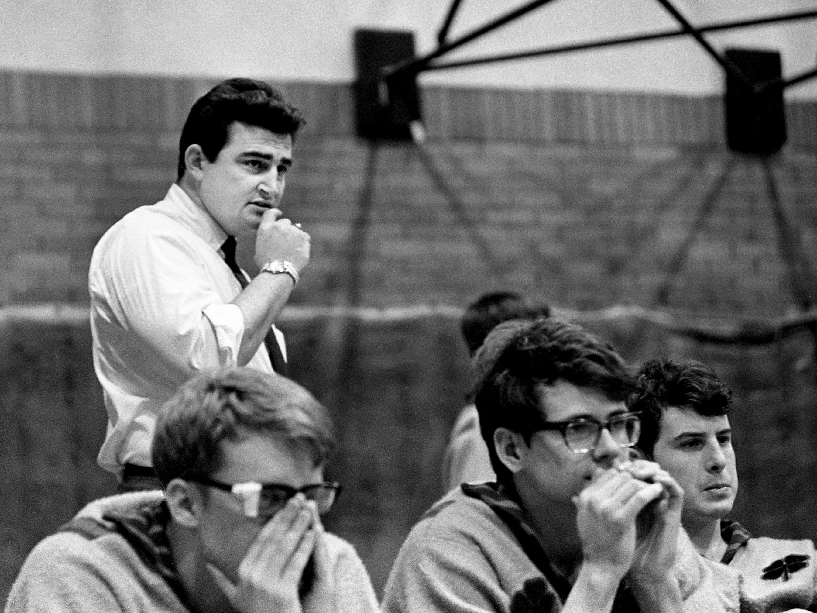 Father Ryan head wrestling coach Joe Drennan, back, keeps his eyes on one of his wrestlers during their 28-12 victory over MBA to capture the NIL and AA-Western titles at home Jan. 30, 1969.
