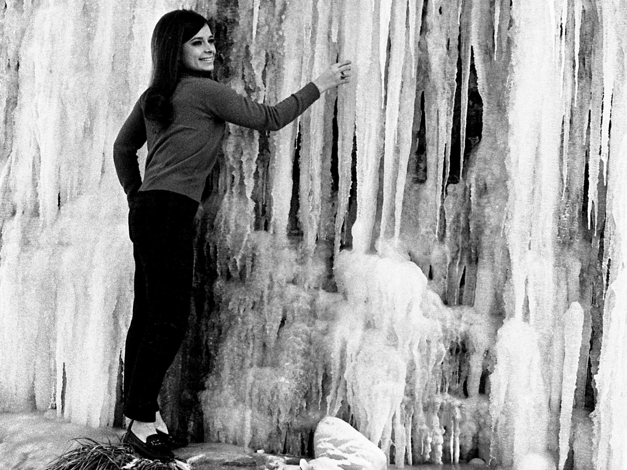 Connie Eaton, a David Lipscomb High School student, reaches for one of the giant icicles that formed on a bluff beside Briley Parkway near Elm Hill Pike as temperatures dropped to a low of 8 degrees Jan. 4, 1969.