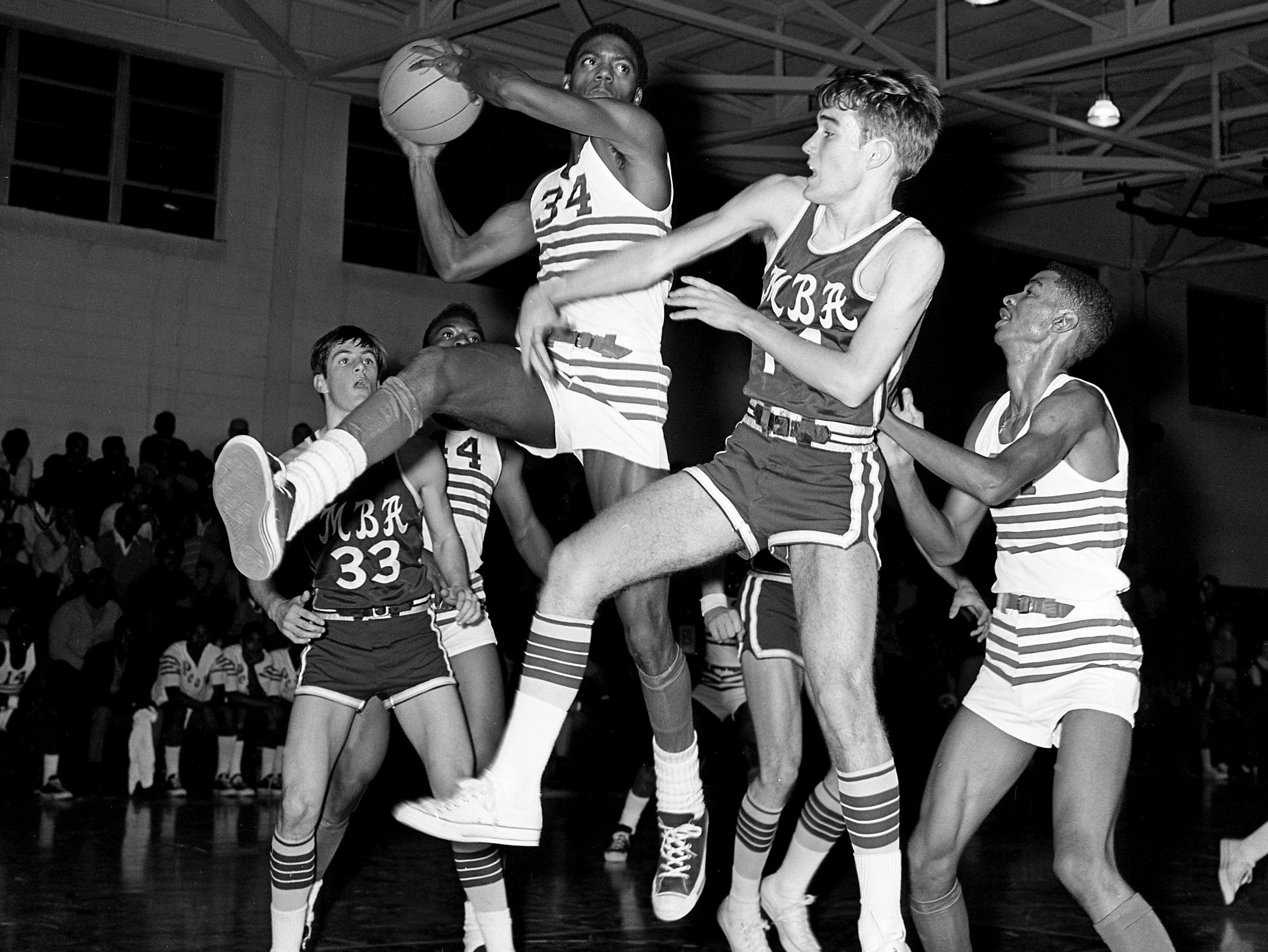 Pearl High's Gary Brooks (34) beats MBA's Edwin Milam, center right, for the rebound as unbeaten Pearl won its ninth straight game in a 58-42 win at home over Big Red on Jan. 3, 1969.