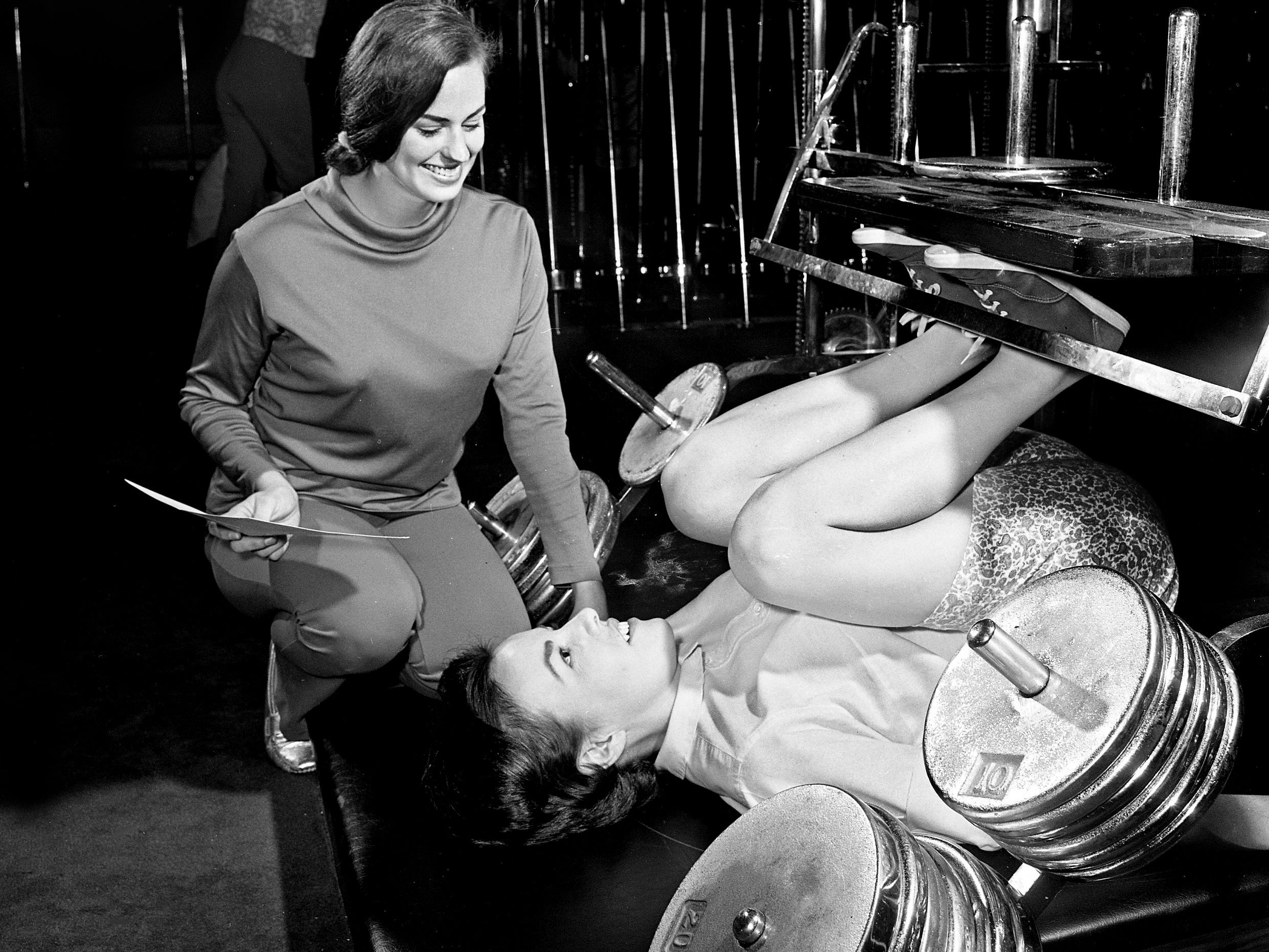 Tennessean reporter Candy McCampbell, bottom, works out on the leg press as instructor Judy McCurley makes sure she is doing it right on a visit to the Cosmopolitan Health Spa in Green Hills on Jan. 8, 1969, for a story on starting exercise for the new year.