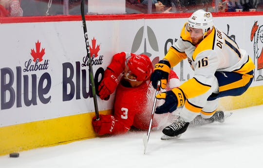 Detroit Red Wings defenseman Nick Jensen (3) slides into the boards while chasing the puck against Nashville Predators left wing Phillip Di Giuseppe (16) in the third period at Little Caesars Arena.