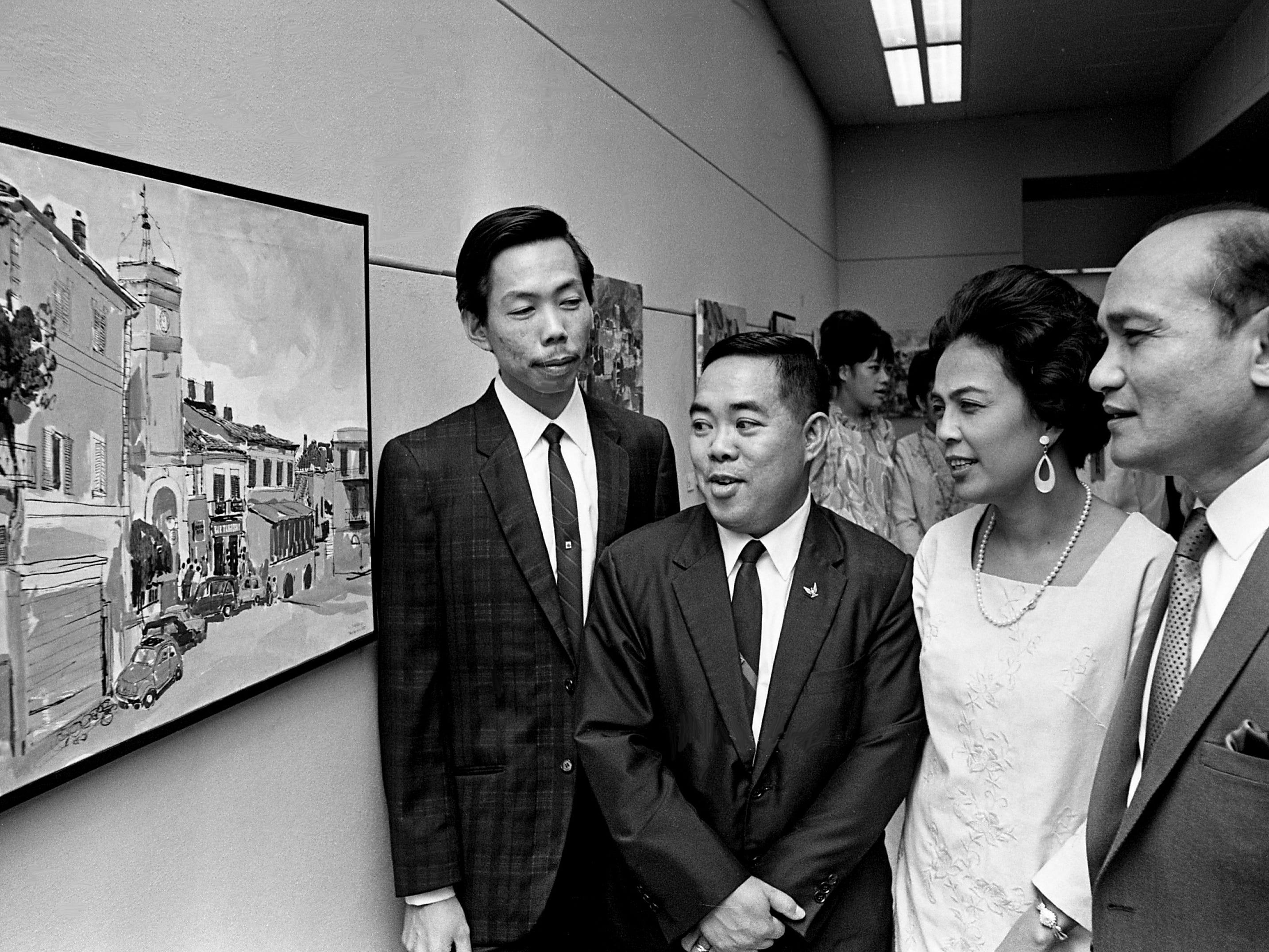 Salvador P. Lopez, right, ambassador from the Philippines to the United States, checks out one of the paintings at the two-man show of painter Lito David, left, and cartoonist Dani Aguila, second from left with his wife, during the opening reception at the Parthenon on Jan. 5, 1969.