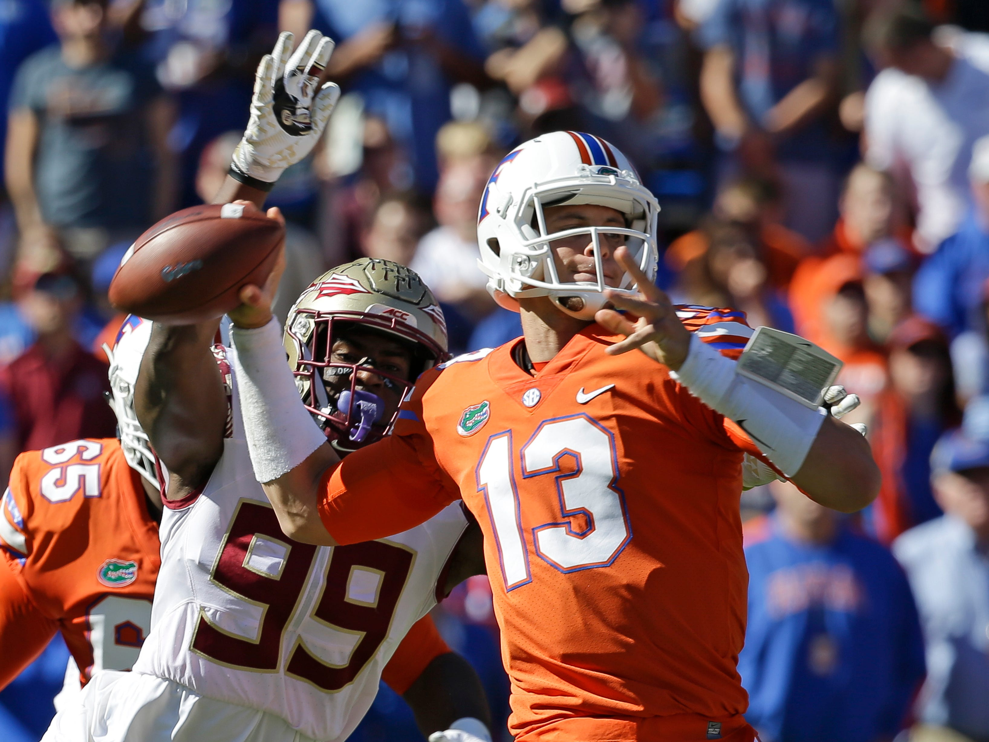 Florida State defensive end Brian Burns (99) strips the ball from the hand of Florida quarterback Feleipe Franks (13) during the first half of an NCAA college football game, Saturday, Nov. 25, 2017, in Gainesville, Fla. Florida State recovered the fumble and scored a touchdown.