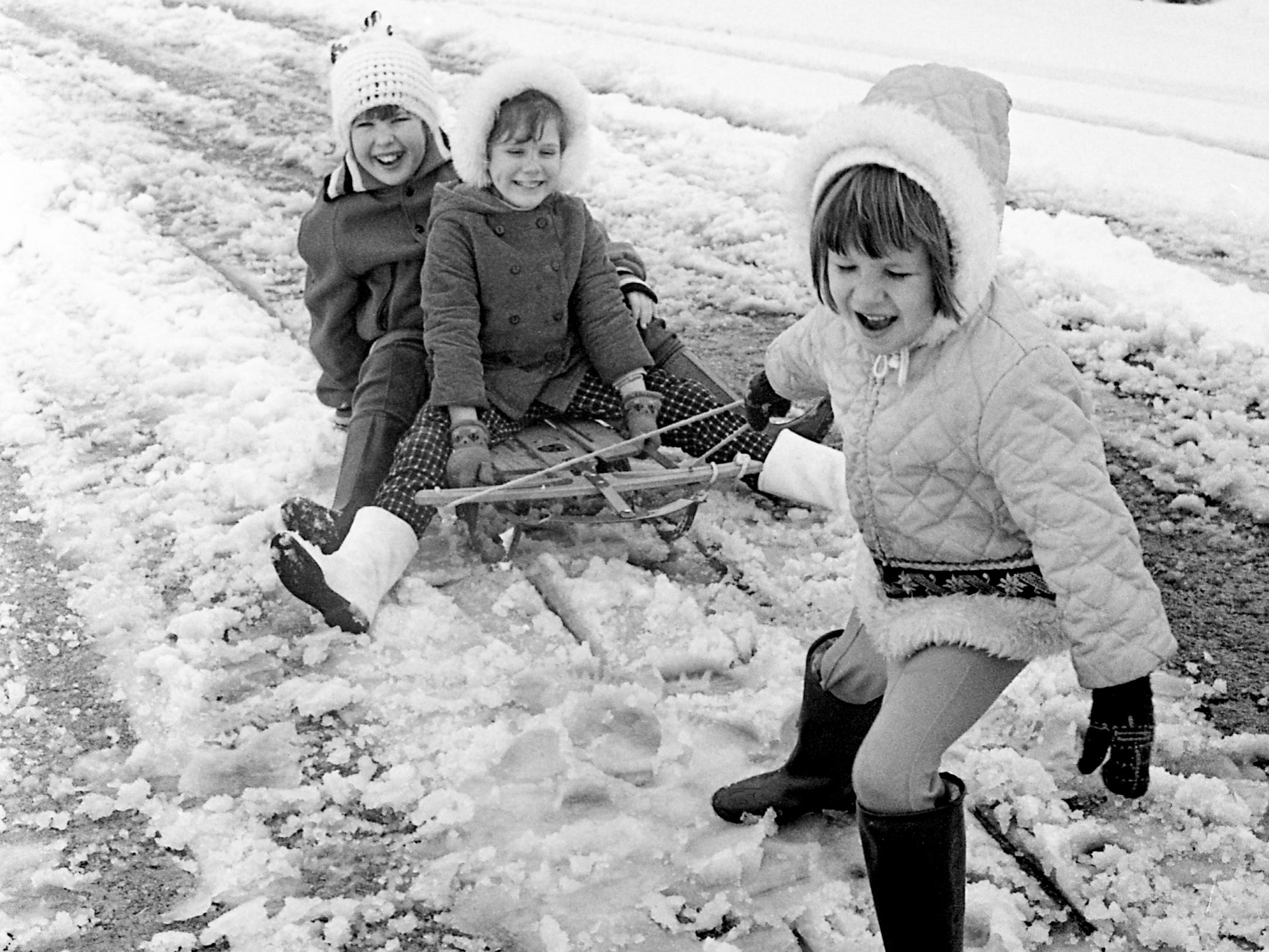 Laurie Campbell takes a turn in pulling sisters Tracey and Kim Cline on their street, Valley Park Drive, after more snow blanketed the city Jan. 27, 1969. The sisters are the daughters of Mr. and Mrs. Billy Cline, and Laurie is the daughter of Mr. and Mrs. Earl Campbell.