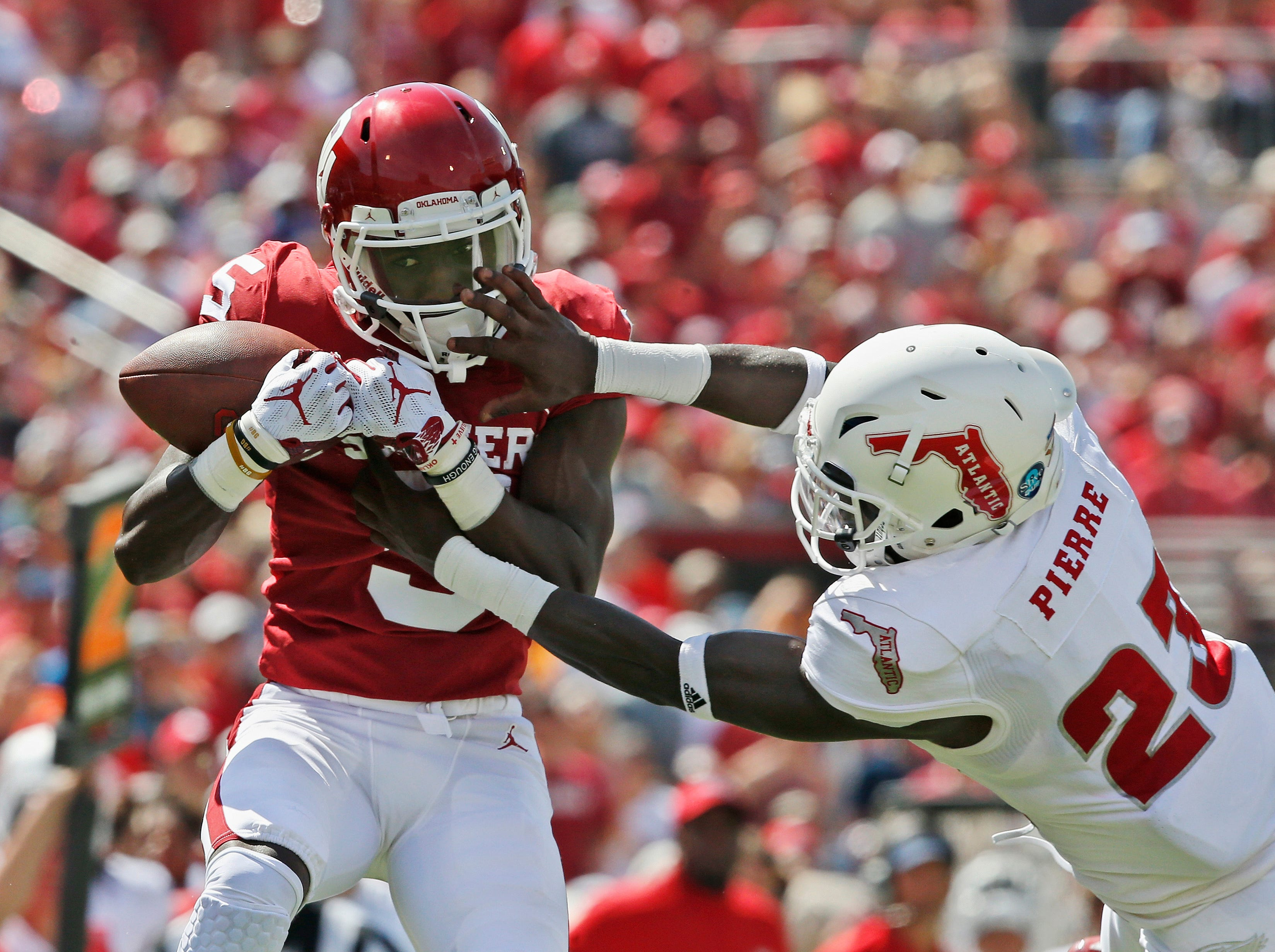 Oklahoma wide receiver Marquise Brown (5) catches a pass defended by Florida Atlantic safety James Pierre (23) in the first half of an NCAA college football game in Norman, Okla., Saturday, Sept. 1, 2018.