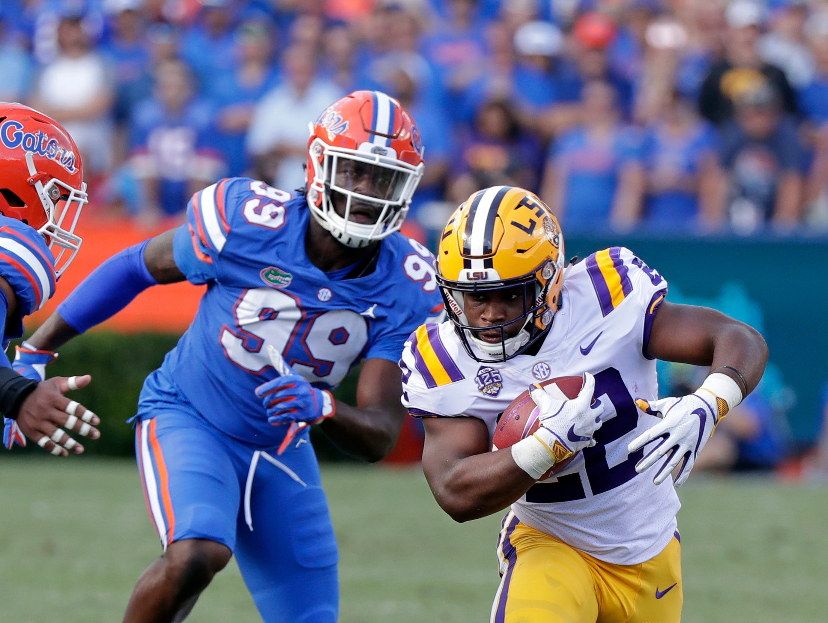 LSU running back Clyde Edwards-Helaire, right, runs past Florida defensive lineman Jachai Polite (99) during the first half of an NCAA college football game, Saturday, Oct. 6, 2018, in Gainesville, Fla.