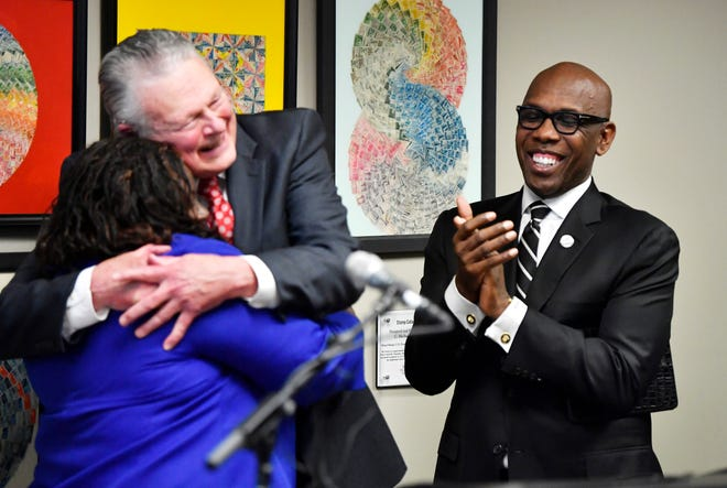 Attorney Charles Bone hugs Juvenile Court Judge Sheila Calloway as Bishop Joseph Walker applauds at a press conference Monday, Jan. 7, 2019, in Nashville, Tenn., after Gov. Bill Haslam granted full clemency to Cyntoia Brown, and set an Aug. 7 release date for her from prison.
