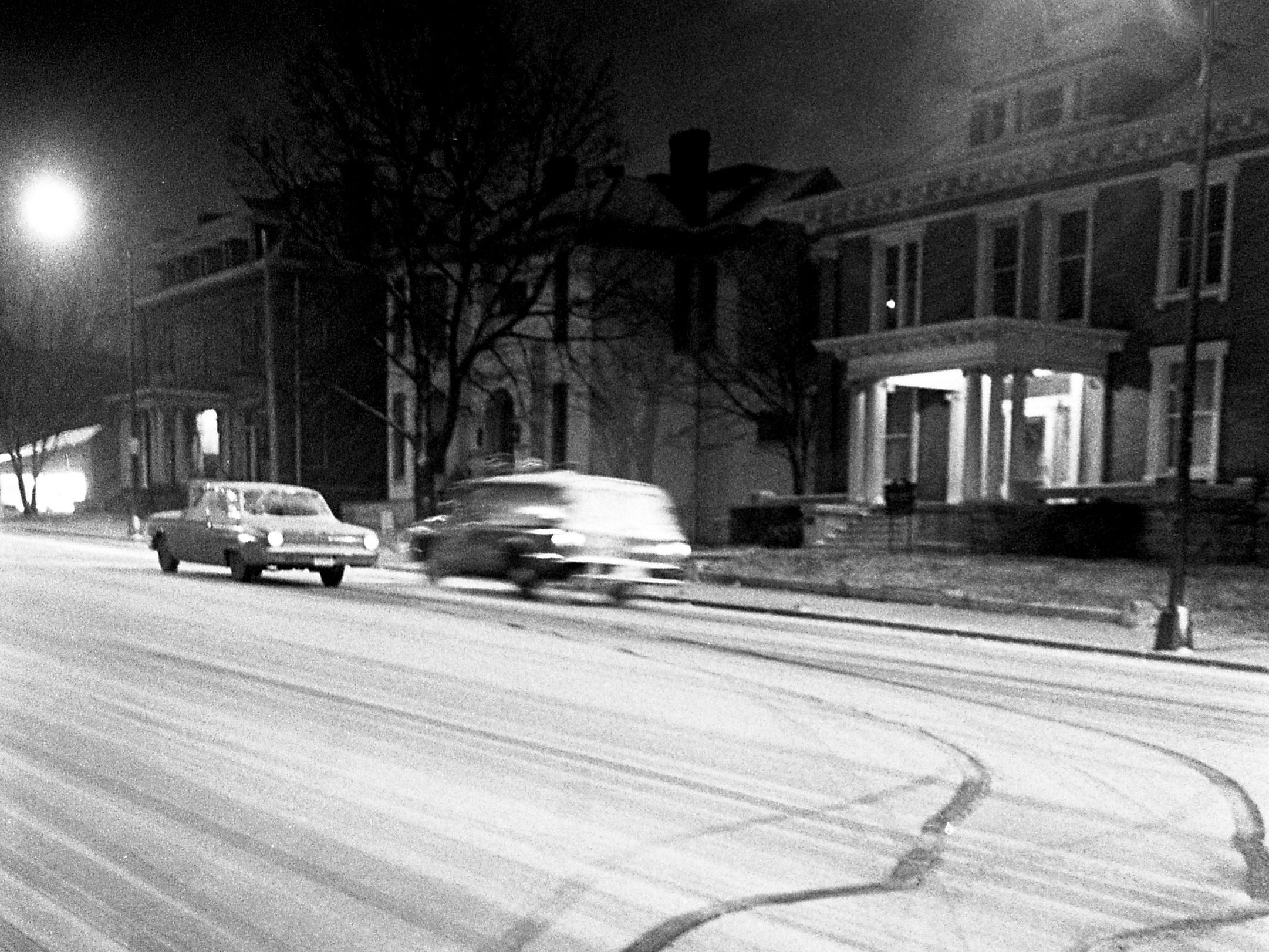 A luckless motorist, stalled on West End Avenue on Jan. 26, 1969, after his car zigzagged erratically across the slick thoroughfare, sits helpless as a police van speeds around him. Such scenes were common on Nashville streets after about 3 inches of snow iced the roads.