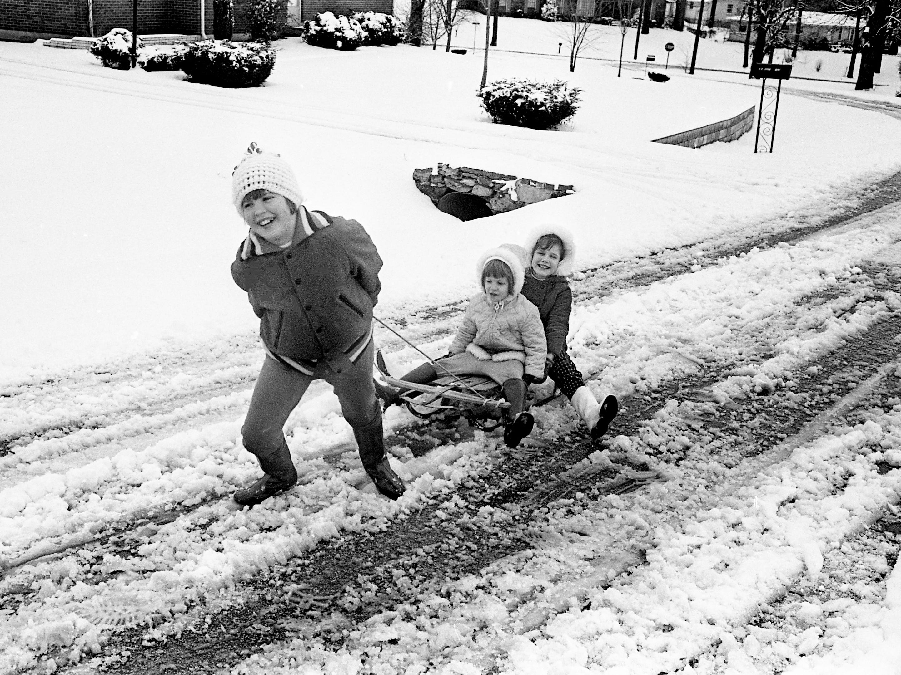 Tracey Cline does all the work as she pulls along her sister, Kim, and friend Laurie Campbell on their street, Valley Park Drive, after more snow blanketed the city Jan. 27, 1969. The sisters are the daughters of Mr. and Mrs. Billy Cline, and Laurie is the daughter of Mr. and Mrs. Earl Campbell.