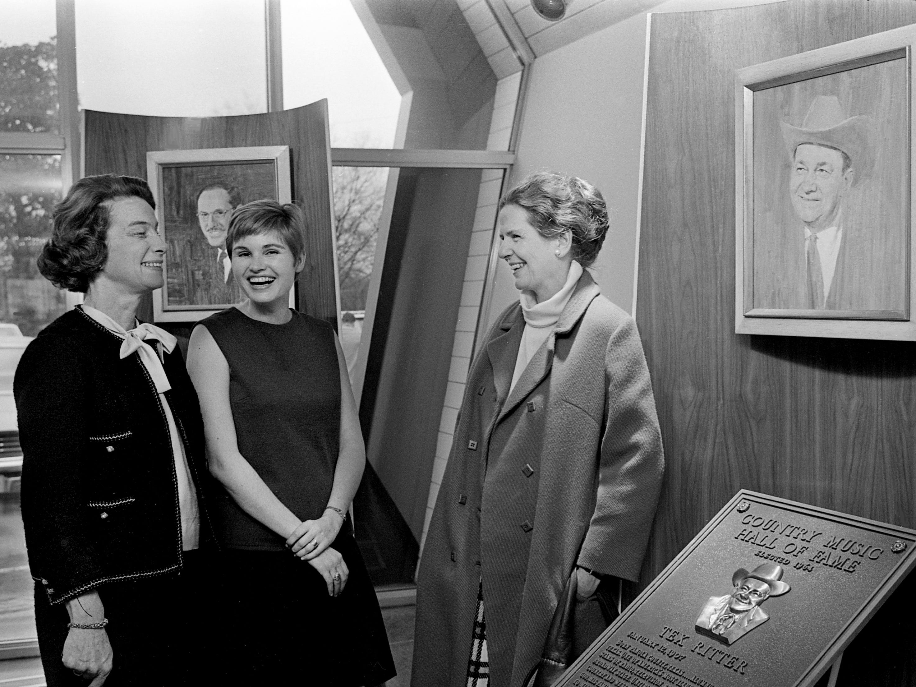 Mrs. B.B. Gullett, left, Mrs. Tom Peebles and Mrs. Charles Trabue Jr., members of the Nashville Bar Auxiliary, check out the plaque of Tex Ritter at the Country Music Hall of Fame after their luncheon at the site Jan. 30, 1969.