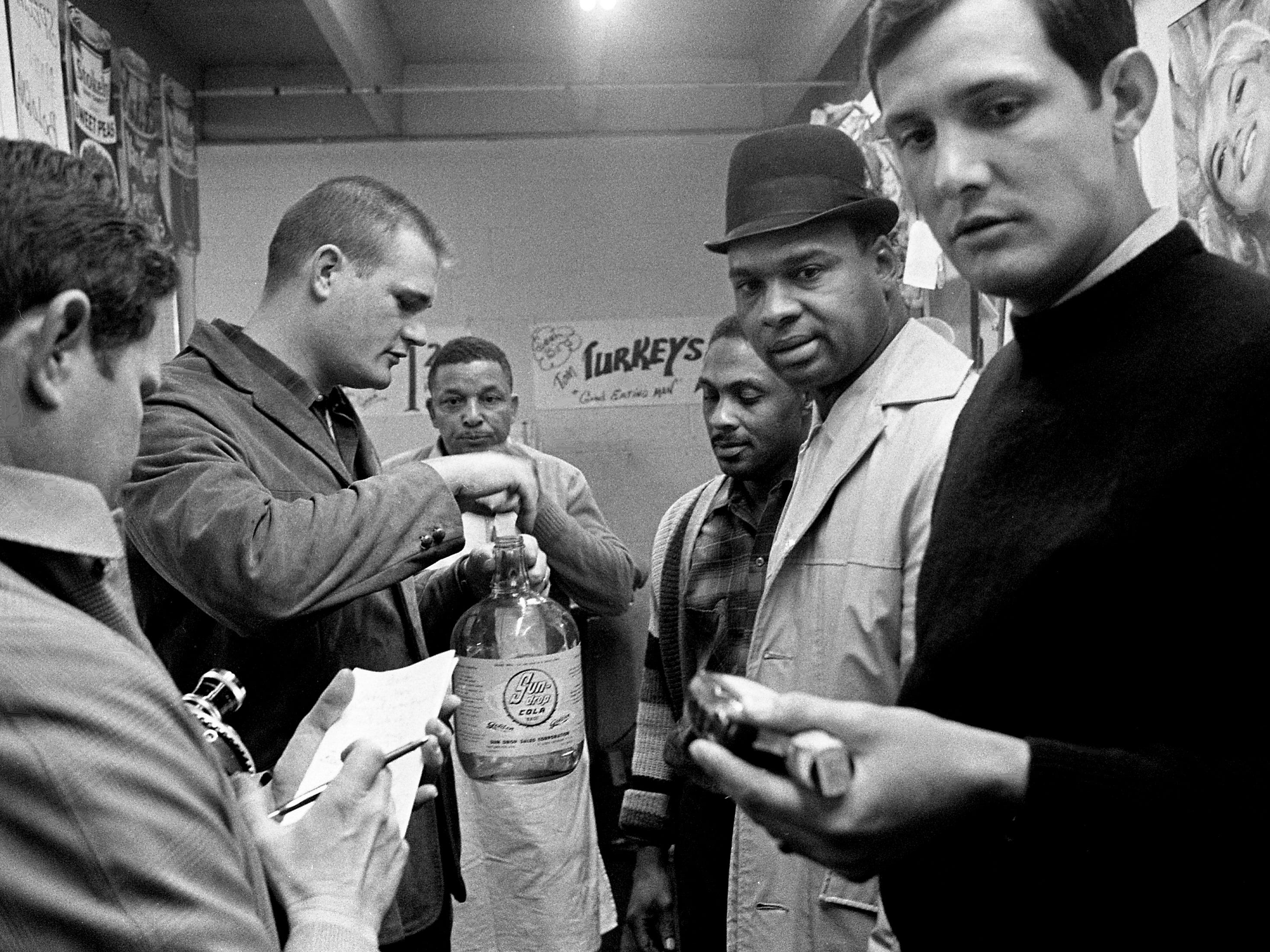 Metro Patrol Sgt. Joe Herrud, second from left, examines a gallon of moonshine whiskey confiscated in a raid at Heiman Street Bi-Rite Market on Jan. 28, 1969. Porter Maple, second from left, 48, and James E. Brook, 43, operator of the store, were charged with possession of untaxed whiskey after Herrud and Patrolmen Luther Summers and Carl Dollarhide, right, found 22 gallons of the moonshine behind the meat counter in a locked safe.