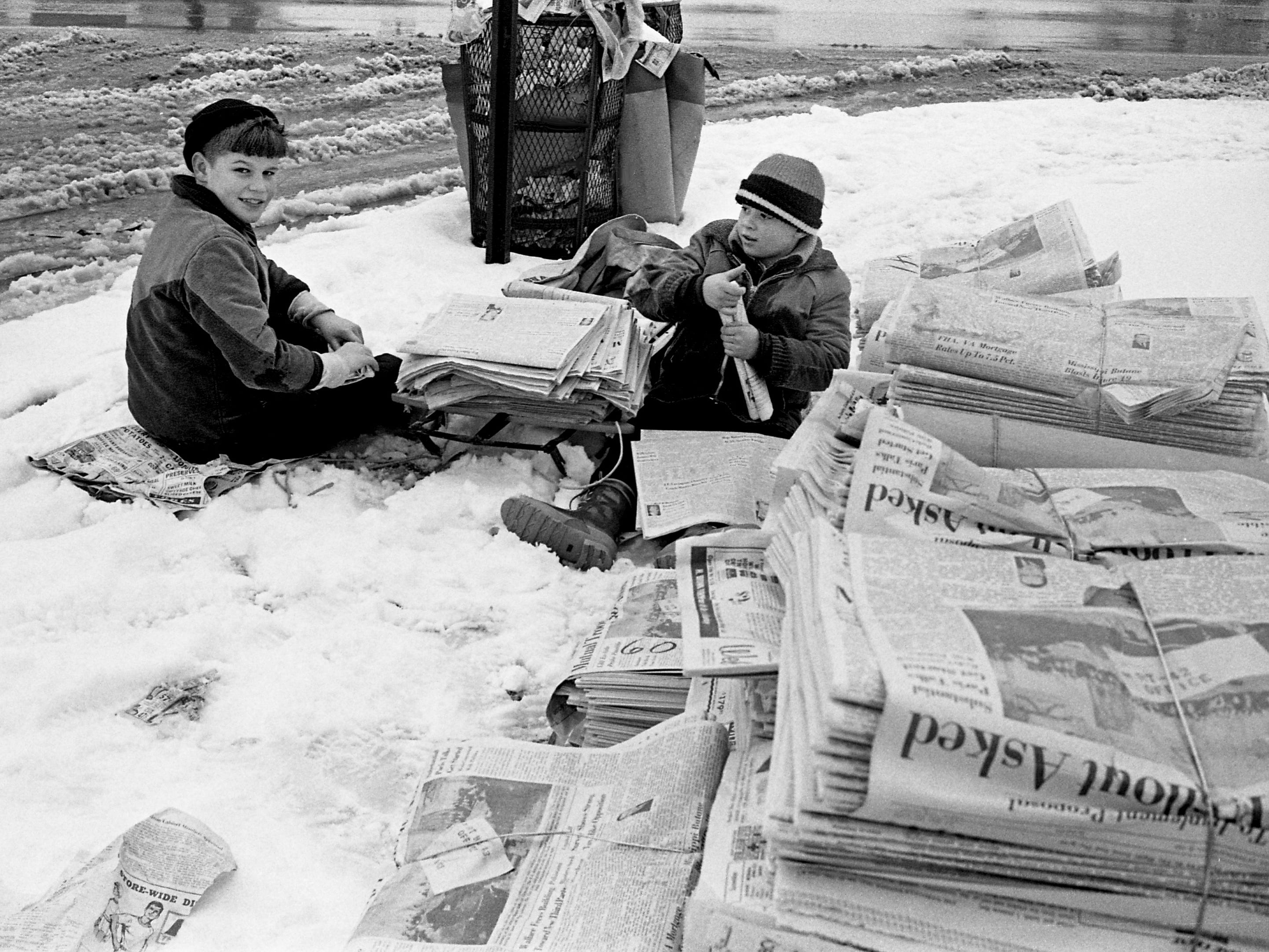Despite a cold and snowy day to be delivering newspapers, David King, left, and Steve Elmore prepare for their routes by using a sled Jan. 27, 1969.