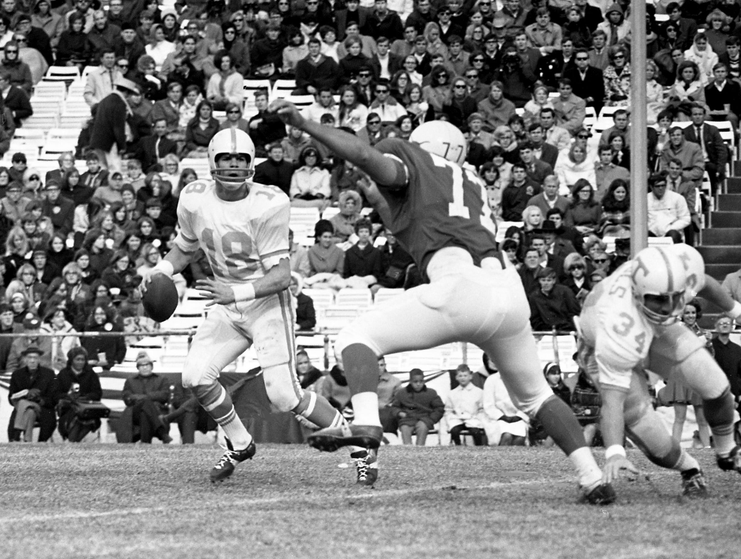 Tennessee quarterback Bubba Wyche (18) looks for a receiver while getting pressure from Texas defensive end Bill Atessis (77) during the Cotton Bowl on Jan. 1, 1969, in Dallas. Tennessee was gored 36-13 by the Longhorns before 72,000 in the 33rd annual New Year's Day classic.