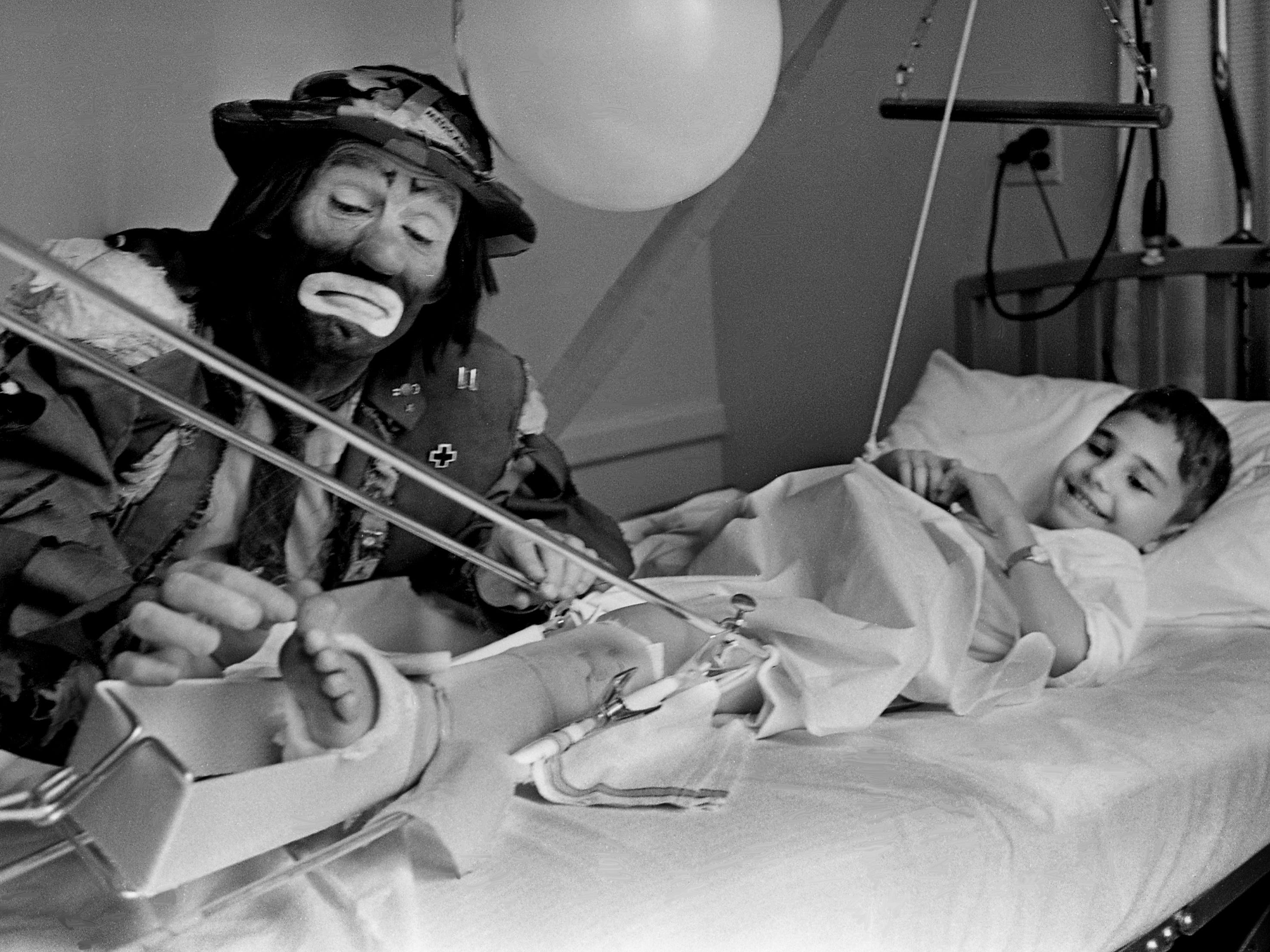 Celebrated clown Emmett Kelly Jr. gets a smile out of a young patient during a visit to the children's ward at Baptist Hospital on Jan. 29, 1969. He is dressed in the costume that his father, the world-famous clown of the same name, made famous.