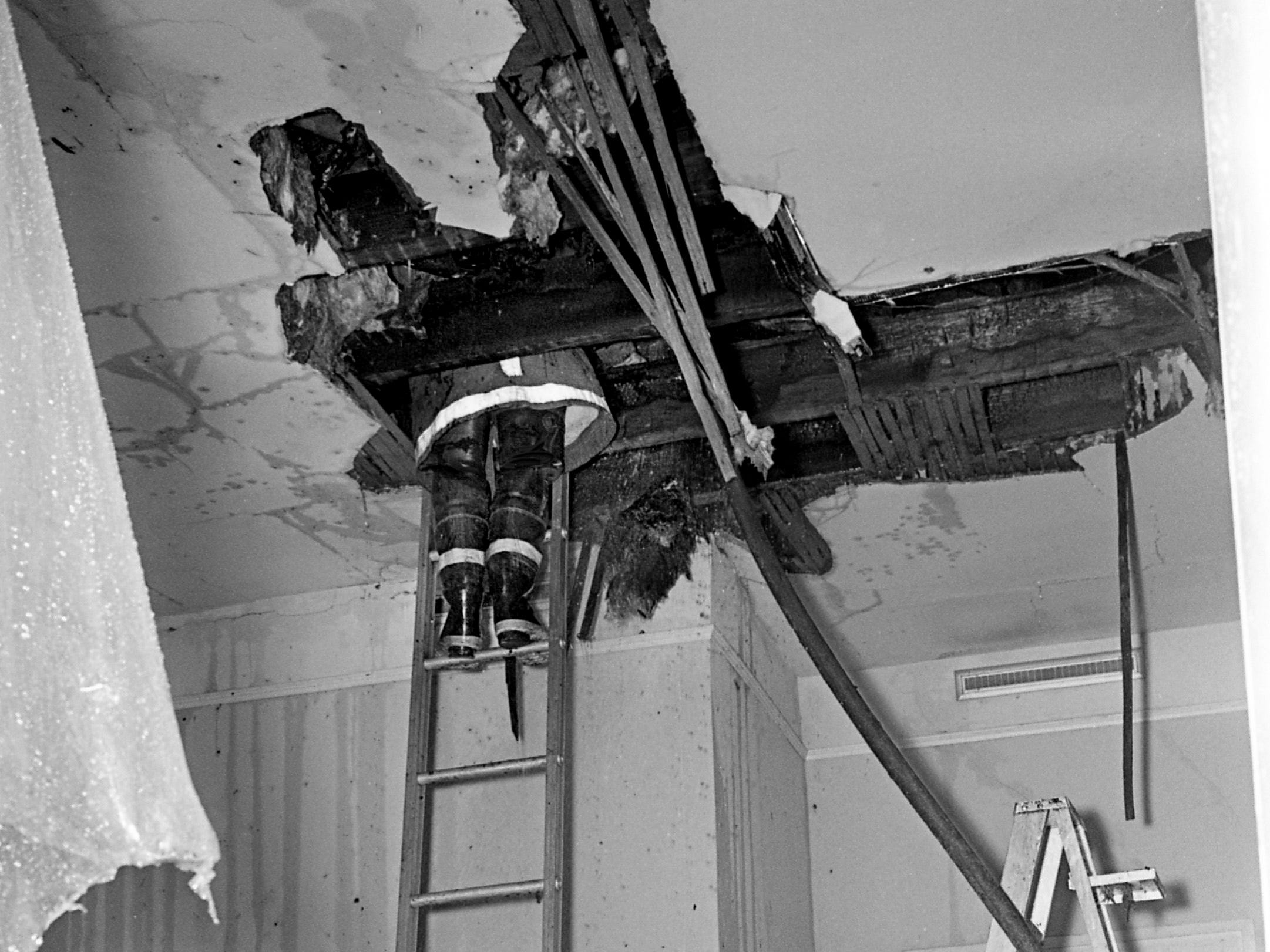 A firefighter climbs through a gaping hole in the ceiling of a room at Travellers' Rest as another wades through water-soaked debris on the floor to battle a fire in the attic Jan. 4, 1969.