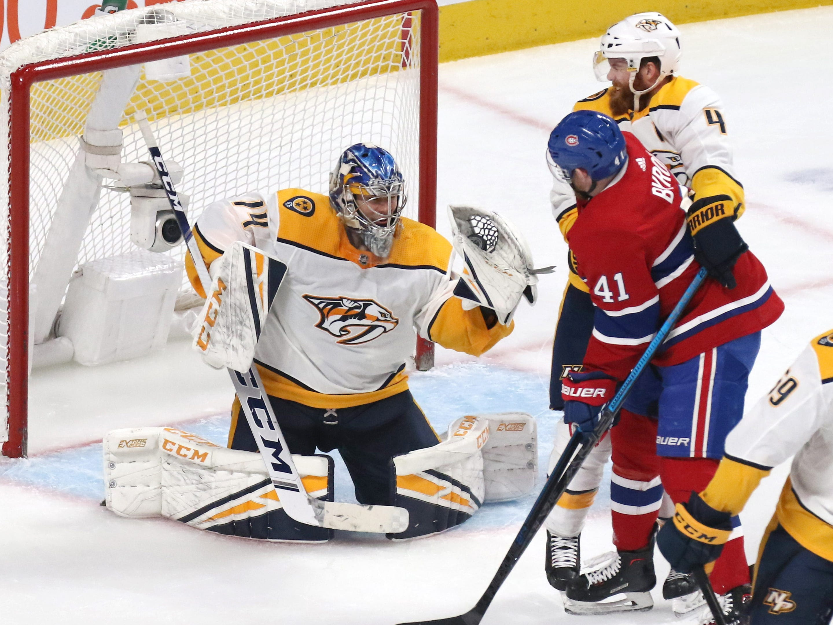 Nashville Predators goaltender Juuse Saros (74) makes a save against Montreal Canadiens left wing Paul Byron (41) as Nashville defenseman Ryan Ellis (4) assists during the third period at Bell Centre.