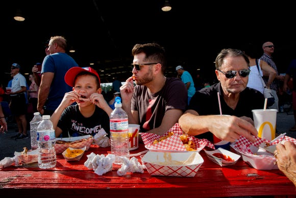 JJ Weatherbie, left, enjoys ribs with his father, Jonas Weatherbie, and grandfather, Charlie Weatherbie, during the 7th Annual Big Swamp Smoke Off & Craft Beer Festival on Saturday, Jan. 5, 2019, at the Collier County Fairgrounds.