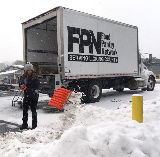 Granville High School student McKenna Beitzel shovels snow to keep the area around the truck clear during the annual Feed the Dream food drive last year. Food donations will again be gathered on Jan. 21 for the Food Pantry Network Serving Licking County at Ross' Granville Market.