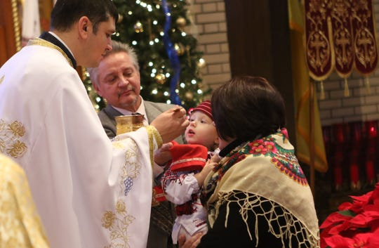 Father Oleksii Holchuk is shown with Katherune Kurpita, 2, at the Ukrainian Orthodox Holy Ascension Church, in Clifton.   Monday, January 7, 2019