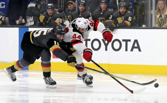 Vegas Golden Knights defenseman Jon Merrill (15) and New Jersey Devils left wing Miles Wood reach to control the puck during the first period of an NHL hockey game Sunday, Jan. 6, 2019, in Las Vegas.