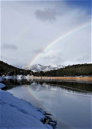 The rainbow is reflected on the thin ice coating at Alto Lake.