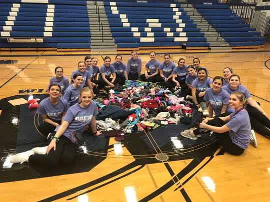 """The Oshkosh West dance team with the winter items collected in the """"Spread the Warmth"""" drive during the Oshkosh West Wildcat Invite."""