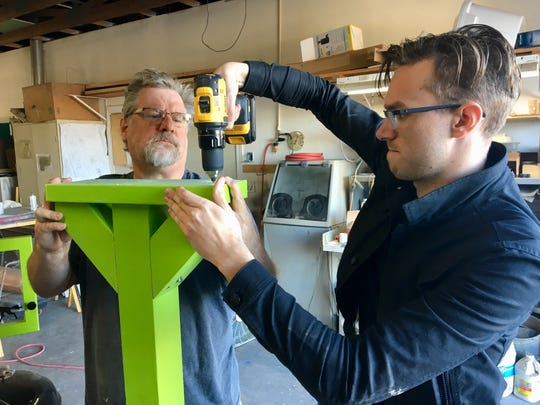 John Penn and Sawyer Bland put together a base and post for a Little Free Library in John's workshop.
