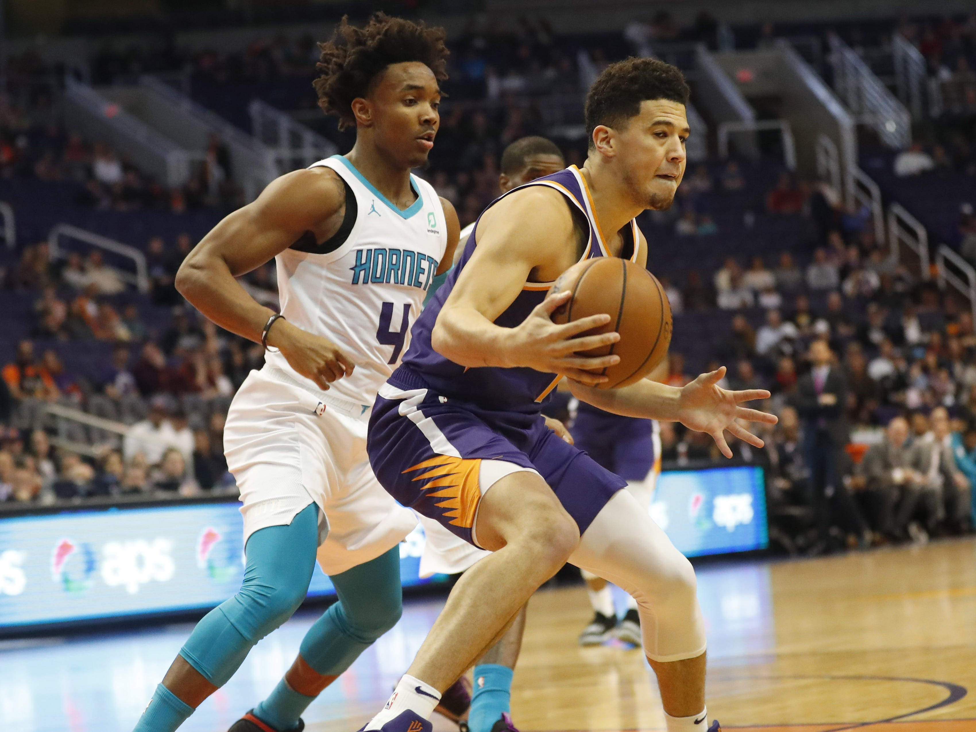 Phoenix Suns guard Devin Booker (1) puts a move on Charlotte Hornets guard Devonte' Graham (4) during the first quarter in Phoenix January 6, 2019.