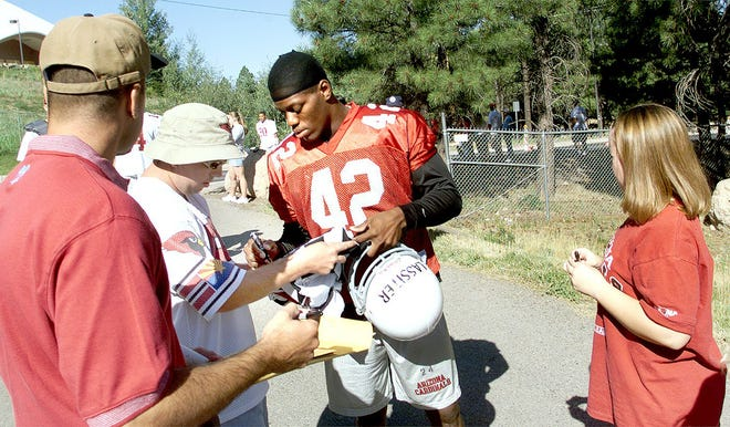 Cardinals safety Kwamie Lassiter stops to sign autographs before a workout with the team.