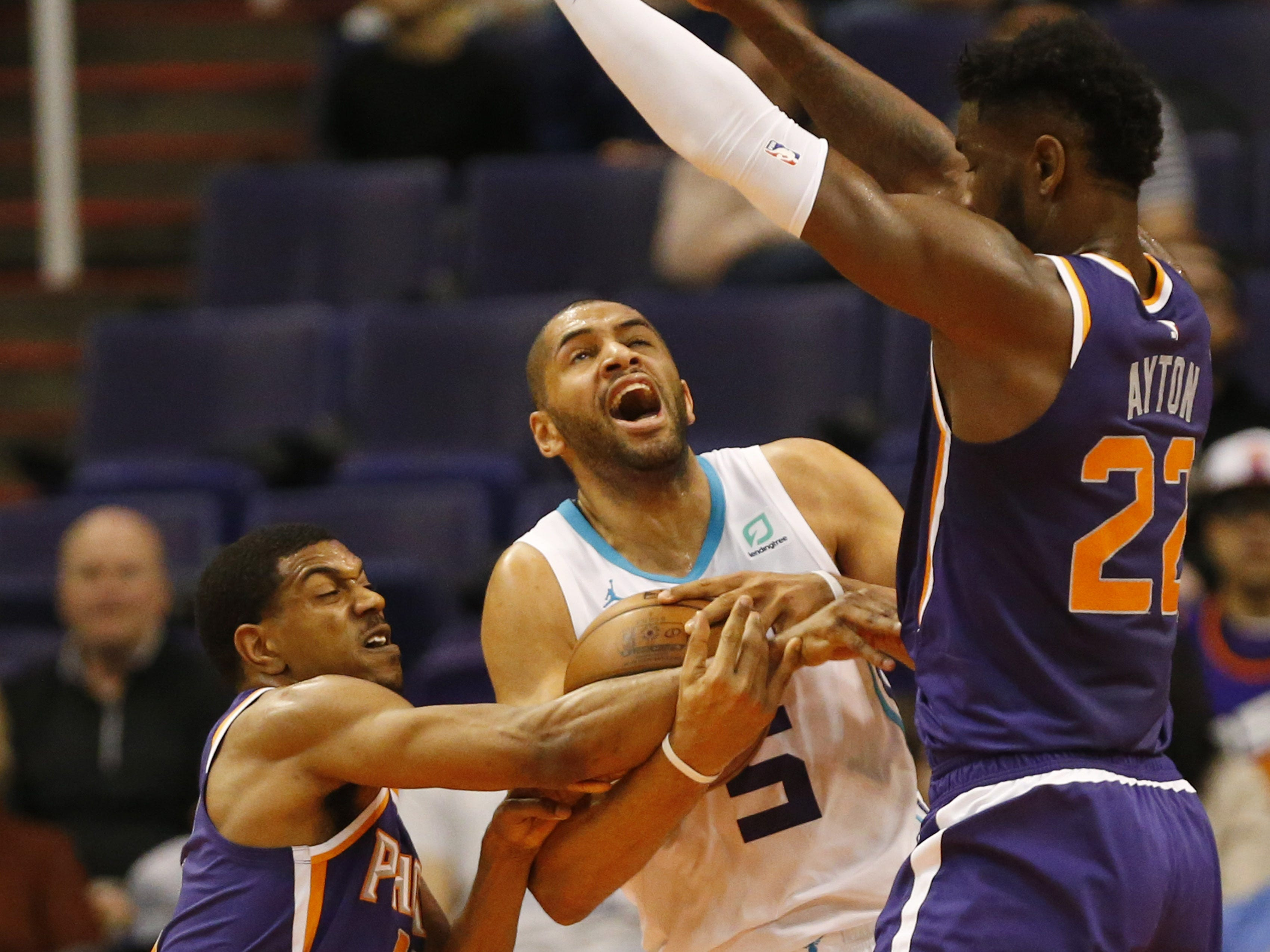 Phoenix Suns guard De'Anthony Melton (14) fouls Charlotte Hornets guard/forward Nicolas Batum (5) during the first quarter in Phoenix January 6, 2019.
