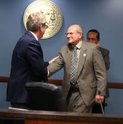 """Robert """"Bob"""" Burns (right) is greeted by Commissioner Boyd Dunn after being voted the new chairman on Jan. 7 at Arizona Corporation Commission offices in Phoenix."""
