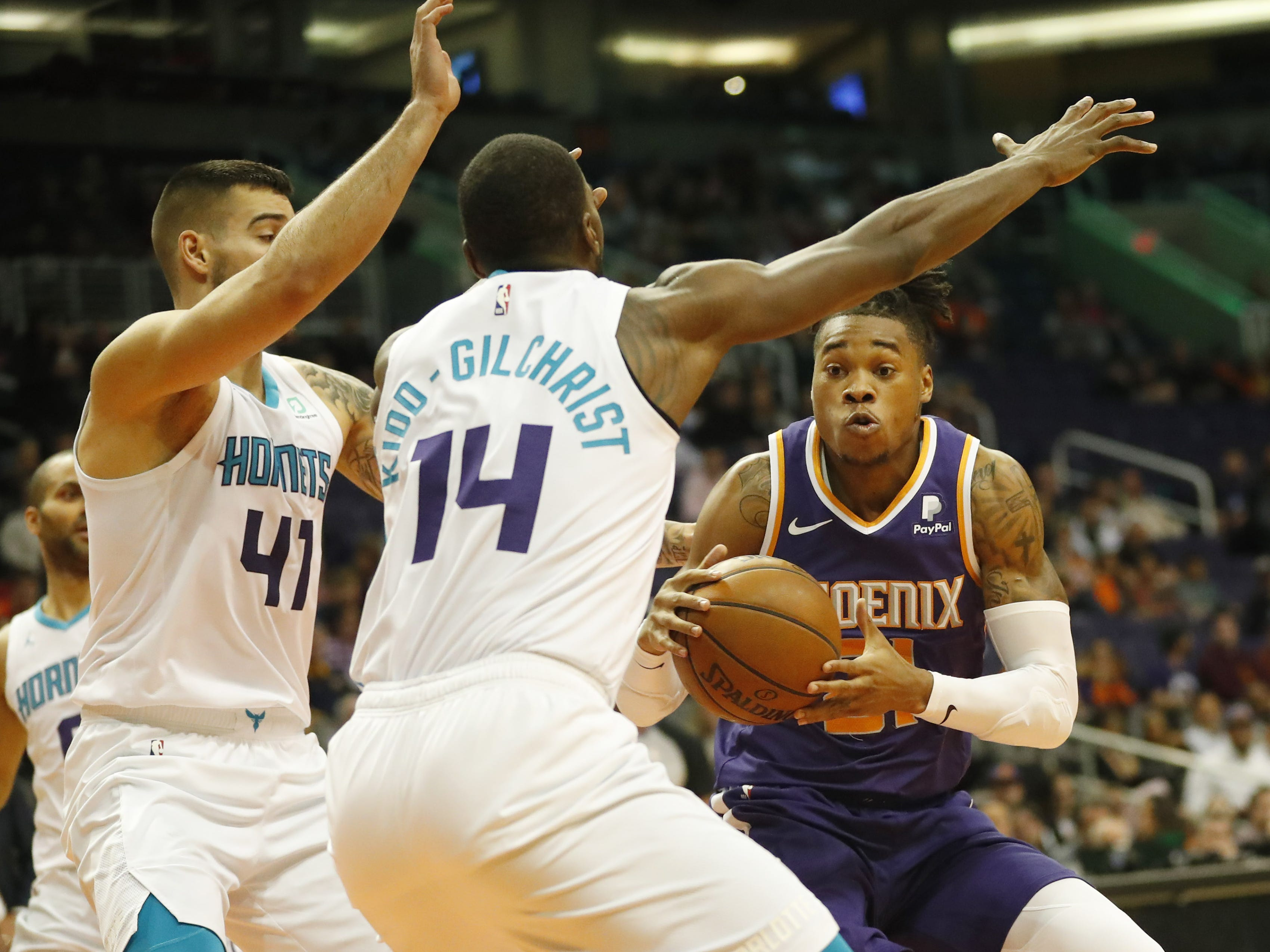 Phoenix Suns forward/center Richaun Holmes (21) puts a move on Charlotte Hornets center Willy Hernangomez (41) and forward Michael Kidd-Gilchrist (14) during the first quarter in Phoenix January 6, 2019.