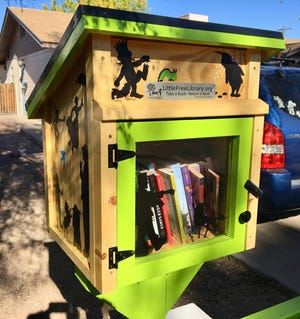 Karina Bland painted a Little Free Library with silhouettes of our favorite book characters.