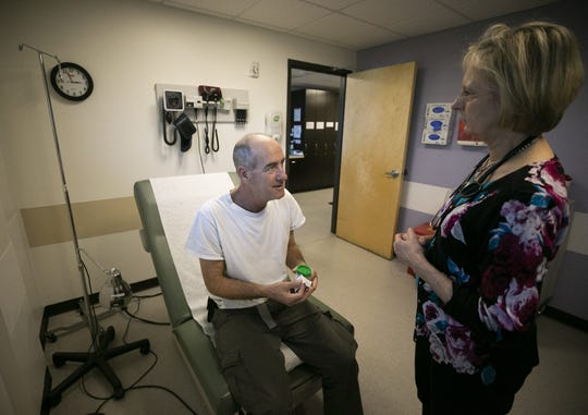 Dr. Diane Elmore examines David Allen at the Circle the City Medical Respite Center in Phoenix on Jan. 4, 2019. Allen, who was homeless, has been at Circle the City for seven months. He has stage 4 lung cancer.