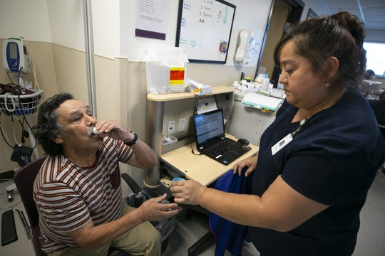 Maximo Gonzales gets his medication from Margarita Mendez, a registered nurse, at the Circle the City Medical Respite Center in Phoenix on Jan. 4, 2019. Gonzales has been at Circle the City Medical Respite Center for a year came because he was living on the street and has stomach cancer.