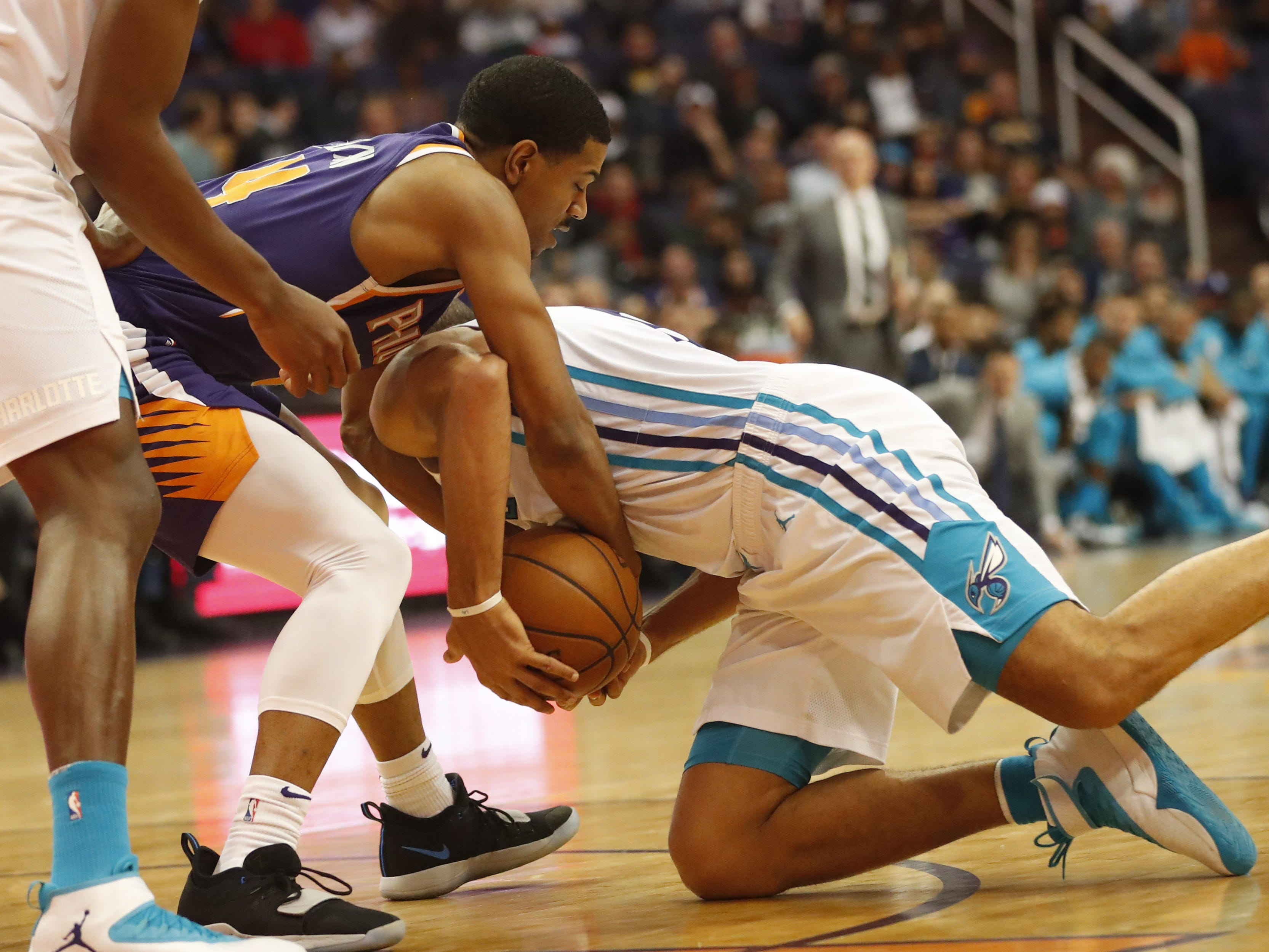 Phoenix Suns guard De'Anthony Melton (14) ties up Charlotte Hornets guard/forward Nicolas Batum (5) for the ball during the second quarter in Phoenix January 6, 2019.