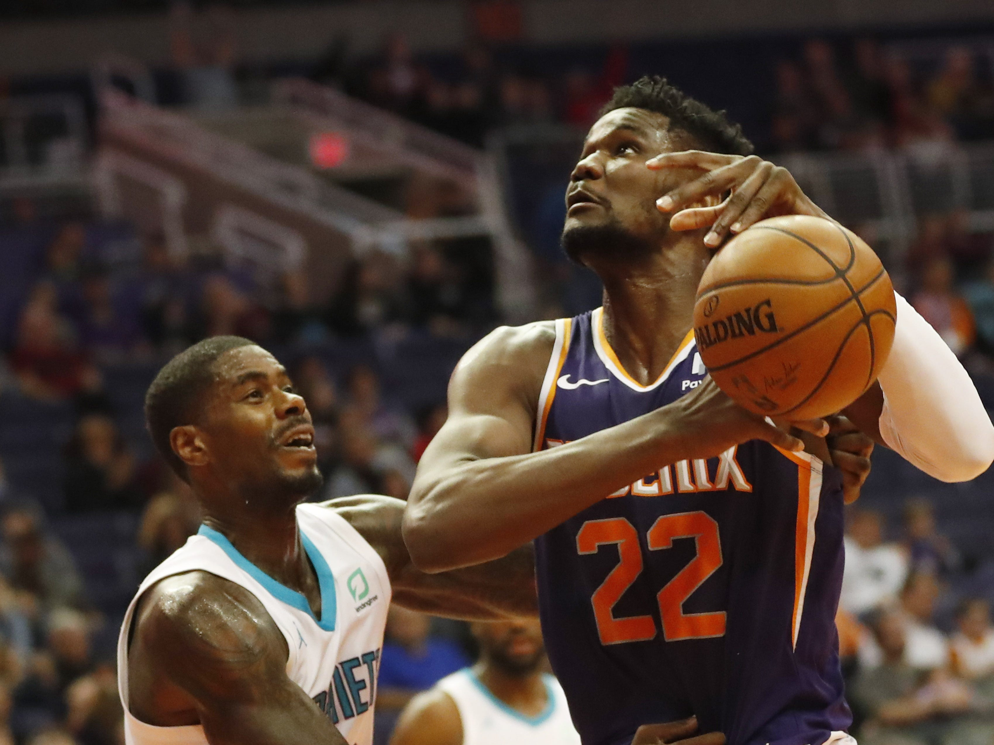 Phoenix Suns center Deandre Ayton (22) is fouled by Charlotte Hornets forward Marvin Williams (2) during the first quarter in Phoenix January 6, 2019.