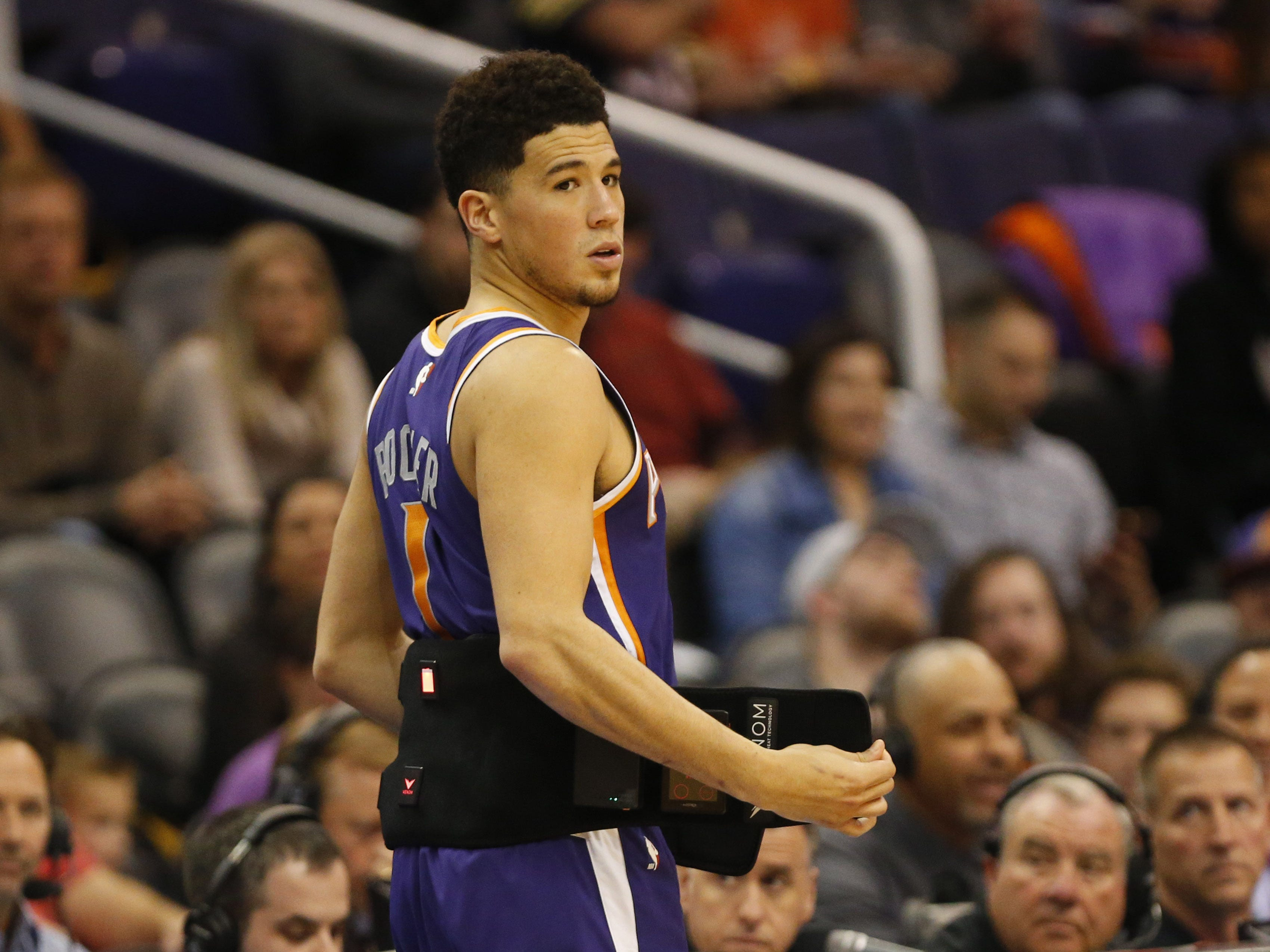 Phoenix Suns guard Devin Booker (1) removes a portable heat and vibration back device before coming in during the second quarter against the Charlotte Hornets in Phoenix January 6, 2019. Booker did not return for the second half due to back spasms.