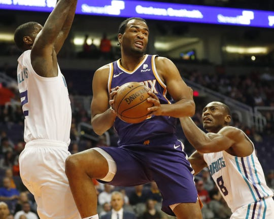 Phoenix Suns forward T.J. Warren (12) looks to pass between Charlotte Hornets forward Marvin Williams (2) and center Bismack Biyombo (8) during the first quarter in Phoenix January 6, 2019.