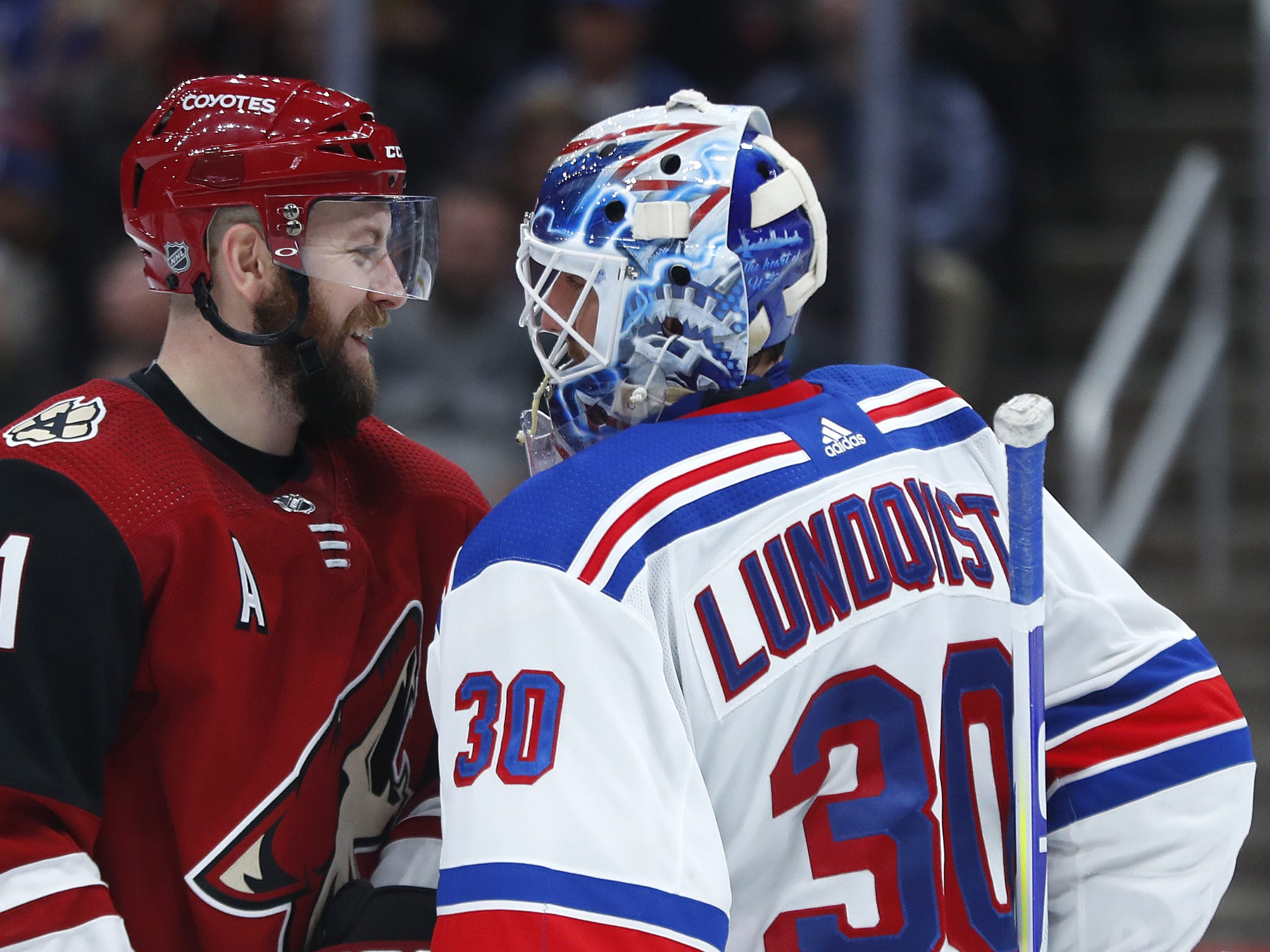 Coyotes' Derek Stepan (21) talks with Rangers' goalie Henrik Lundqvist (30) during the second period at Gila River Arena in Glendale, Ariz. on January 6, 2019.