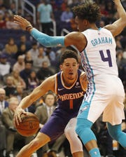 Phoenix Suns guard Devin Booker (1) looks to get past Charlotte Hornets guard Devonte' Graham (4) during the second quarter in Phoenix January 6, 2019.