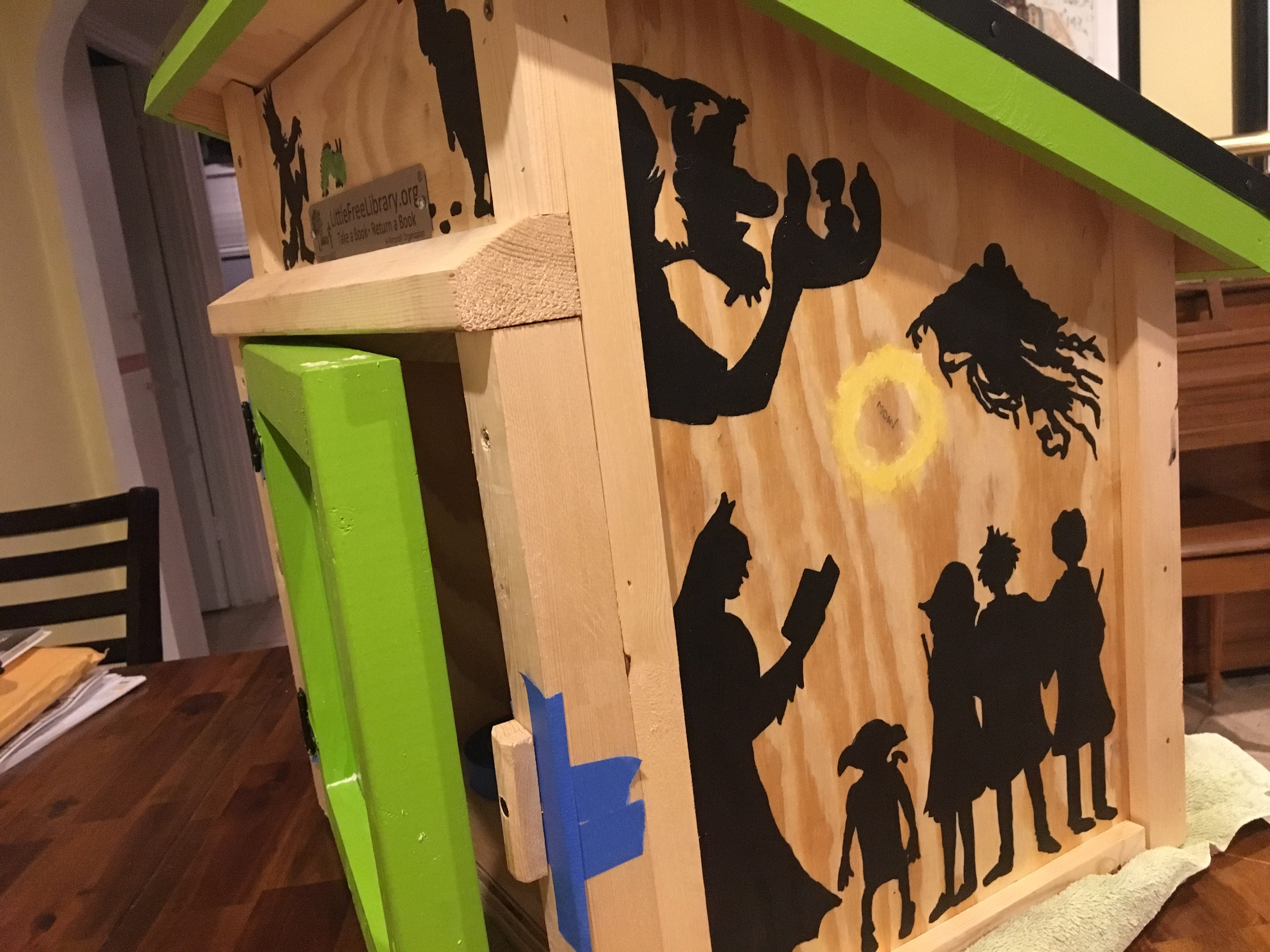 "She painted the Little Free Library with silhouettes of their favorite book characters: the Big Friendly Giant, the young wizards from the Harry Potter series, Peter from ""The Snowy Day."""