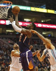 Phoenix Suns center Deandre Ayton (22) lays the ball in while fouled by Charlotte Hornets center Willy Hernangomez (41) during the second quarter in Phoenix January 6, 2019.