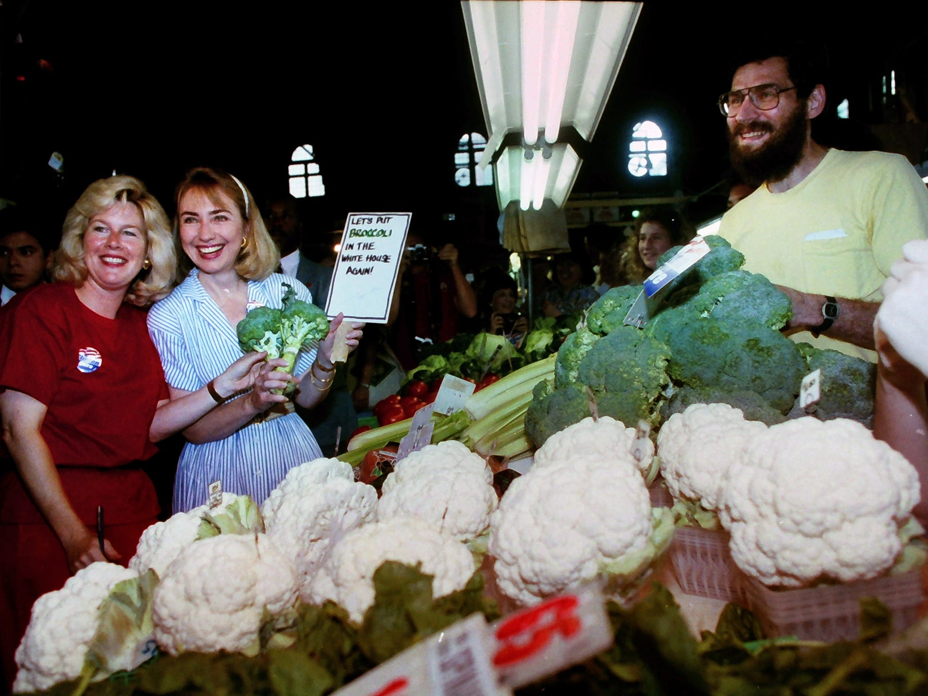 Tipper Gore, left, and Hillary Clinton, second from left, pose with a Central Market vendor holding a sign promoting broccoli during a visit to York July 18, 1992. Hillary Clinton and Tipper Gore accompanied their husbands, Dem nominees Bill Clinton and Al Gore, on a 1,000-mile bus trip after winning their party's nod in July 1992.