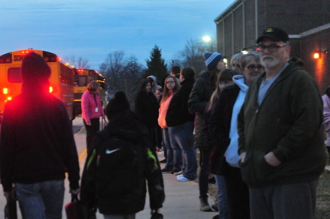 Parents and community members line up to greet Dennis Intermediate School students arriving Monday morning for the first day of class after Christmas break.